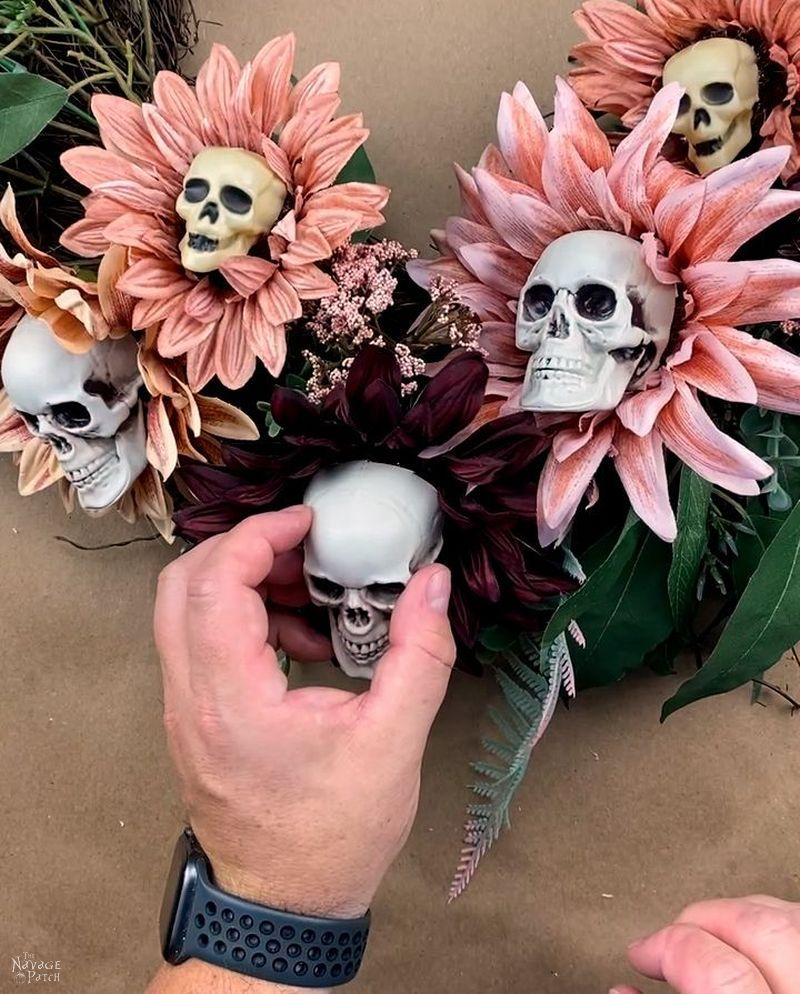 man stick a cut plastic skull with glue on it onto a sunflower on a wreath