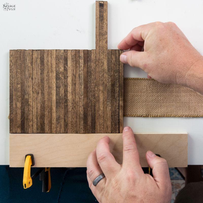 gluing wood dowels onto burlap