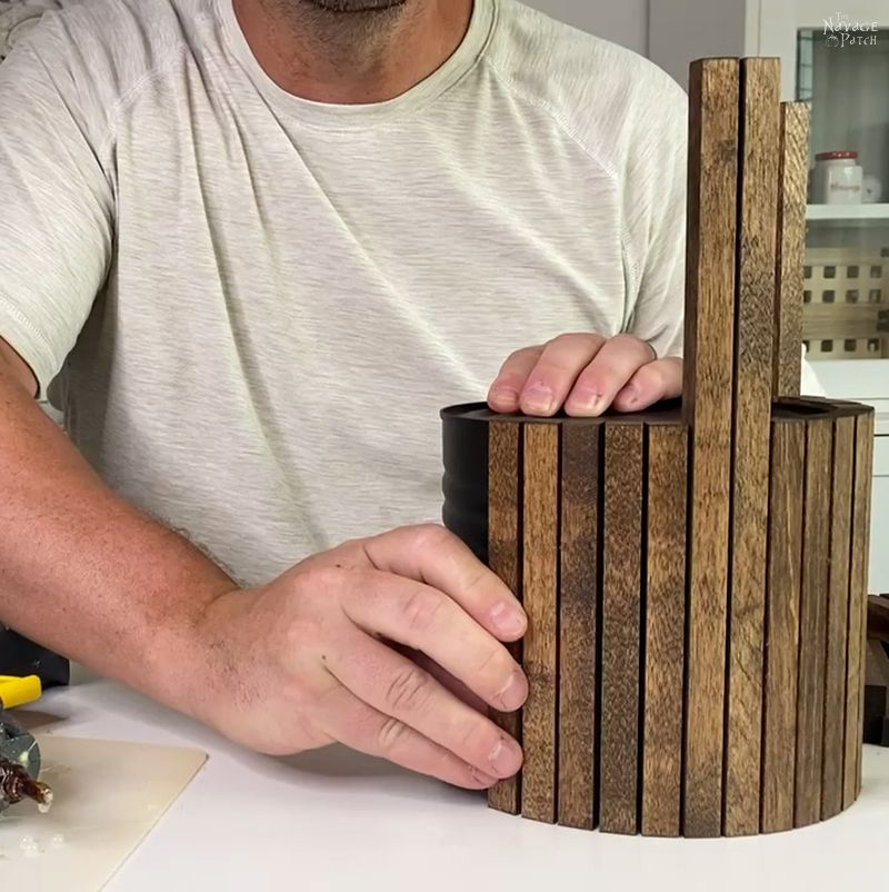 pressing a wood dowel against a coffee can
