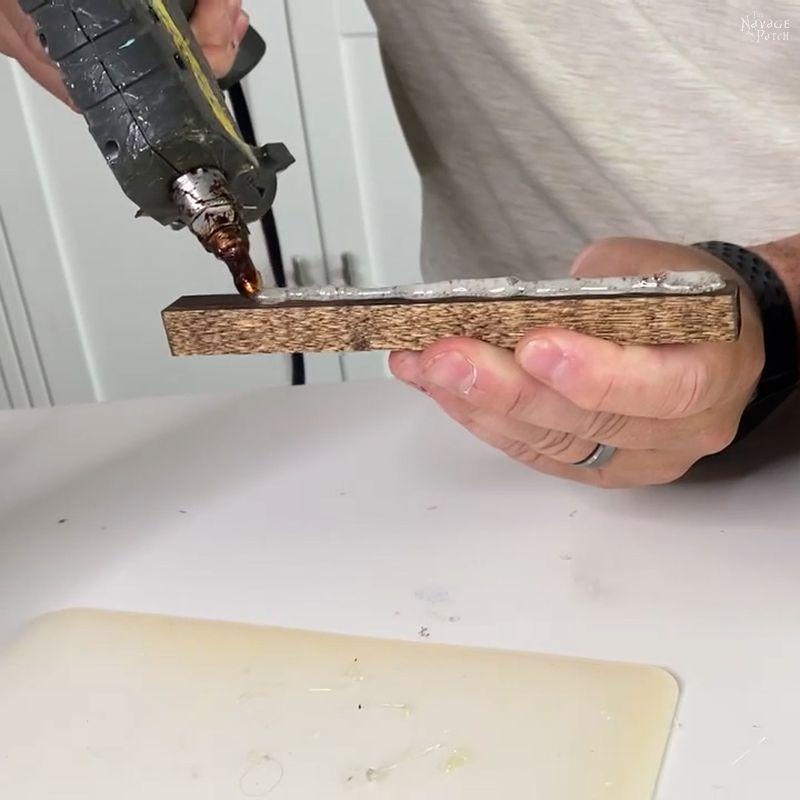 man putting hot glue on a wood dowel
