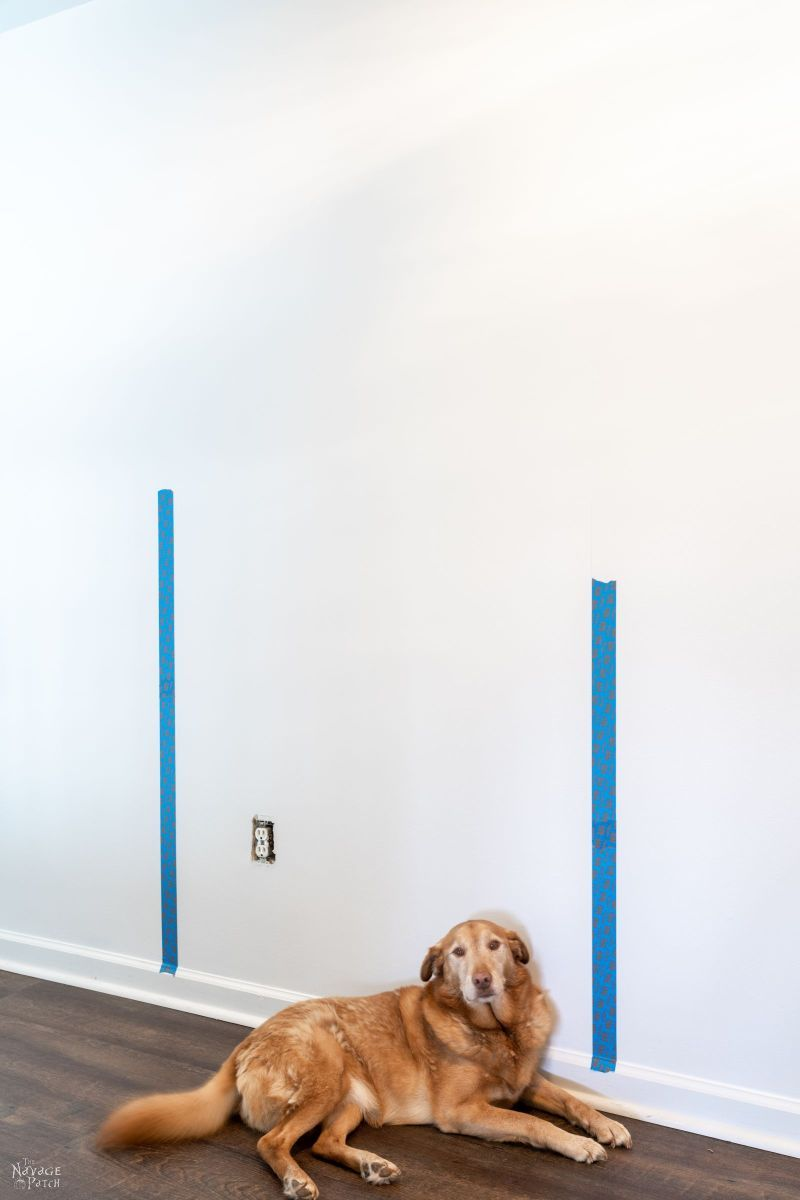 putting blue tape on a wall before painting