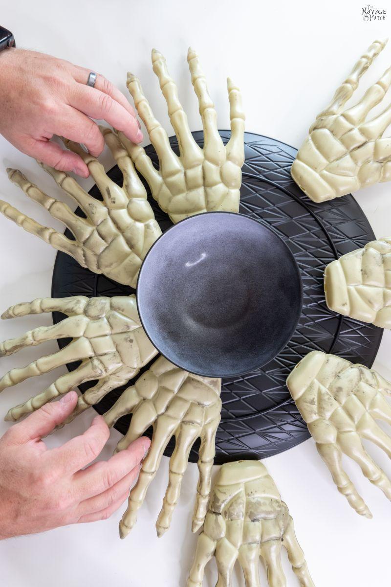 assembling plastic skeleton hands around a platter
