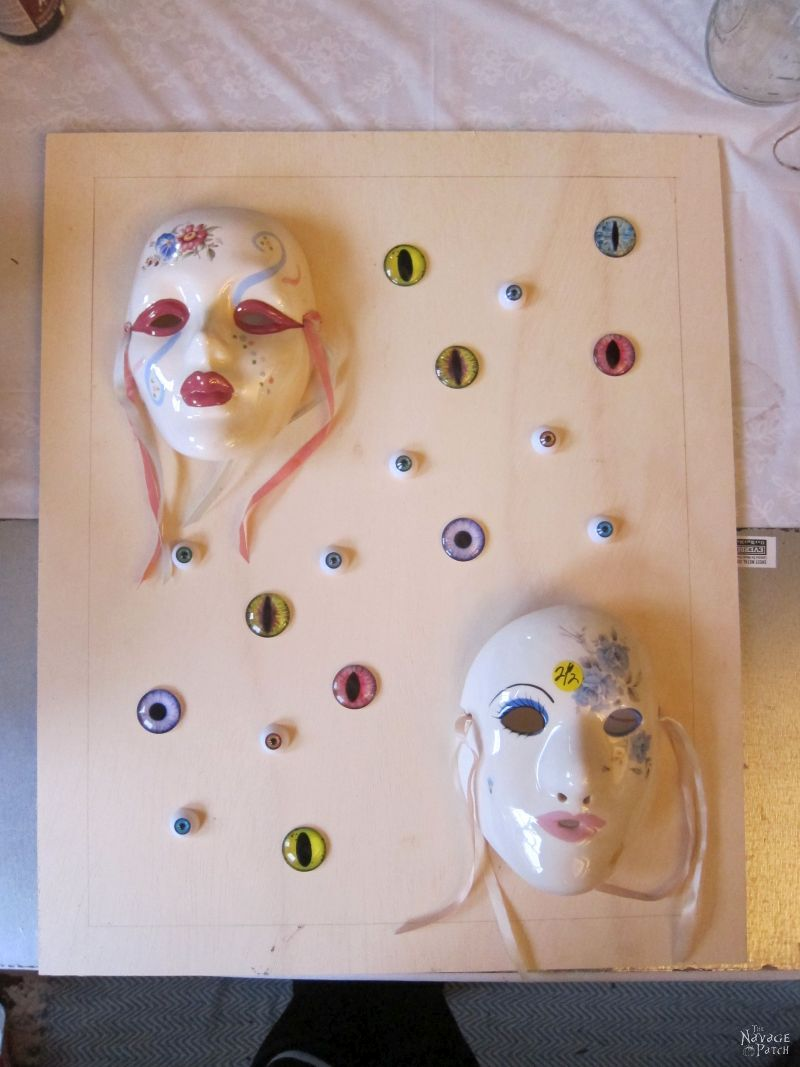 glass eyes and porcelain masks on a piece of plywood
