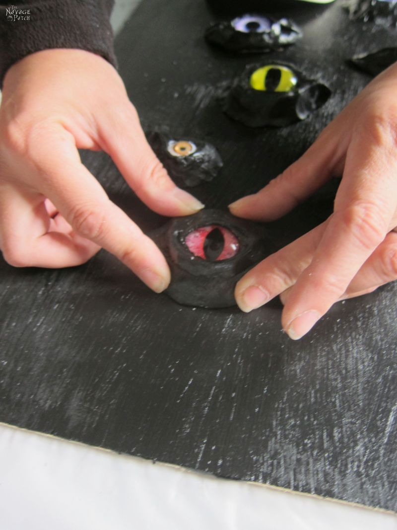 gluing clay eye sockets to plywood