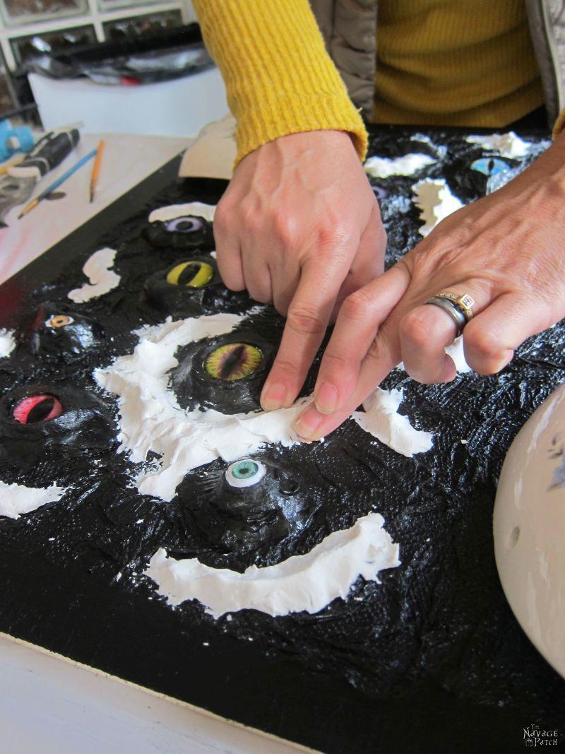 adding air clay to a glass eye halloween craft