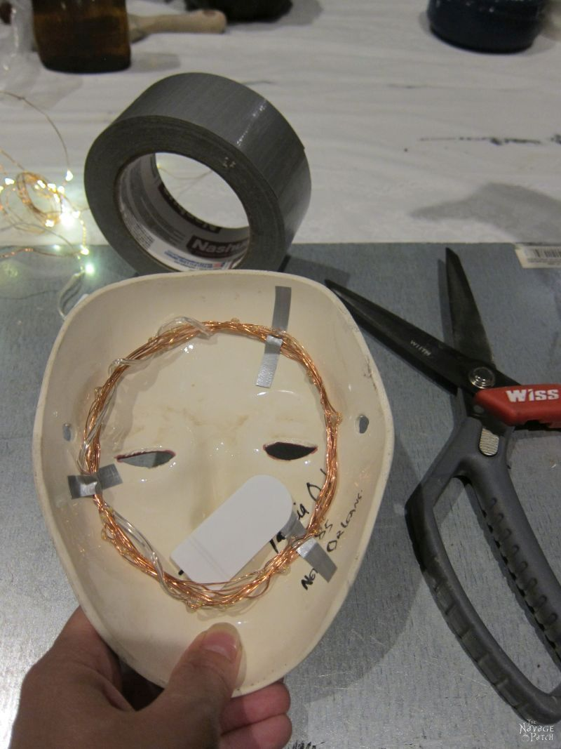 taping fairy lights behind a porcelain mask