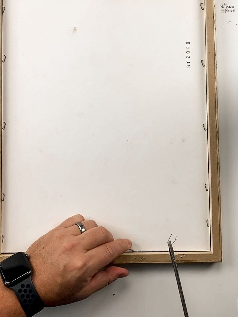 man removing the backing from a picture frame