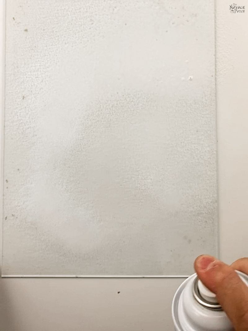 man cleaning the glass from a picture frame