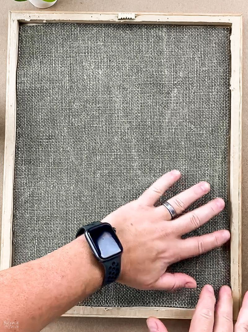 man placing burlap in a picture frame