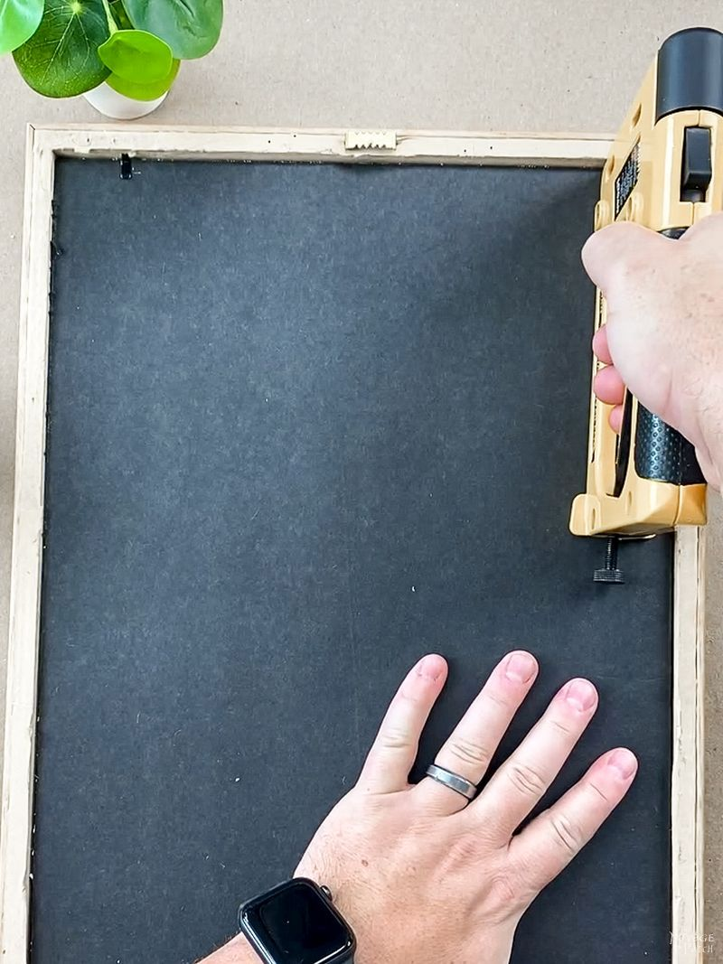 man using a point driver on a picture frame