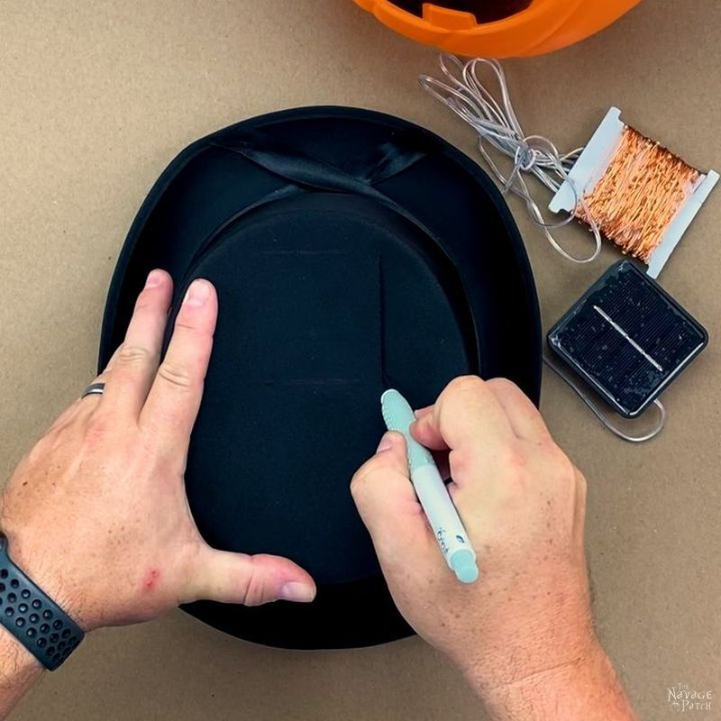 man cutting a hole in a hot hat with an x-acto knife