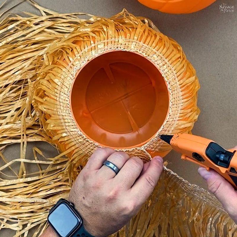 man gluing a grass table skirt around a plastic pumpkin candy pail