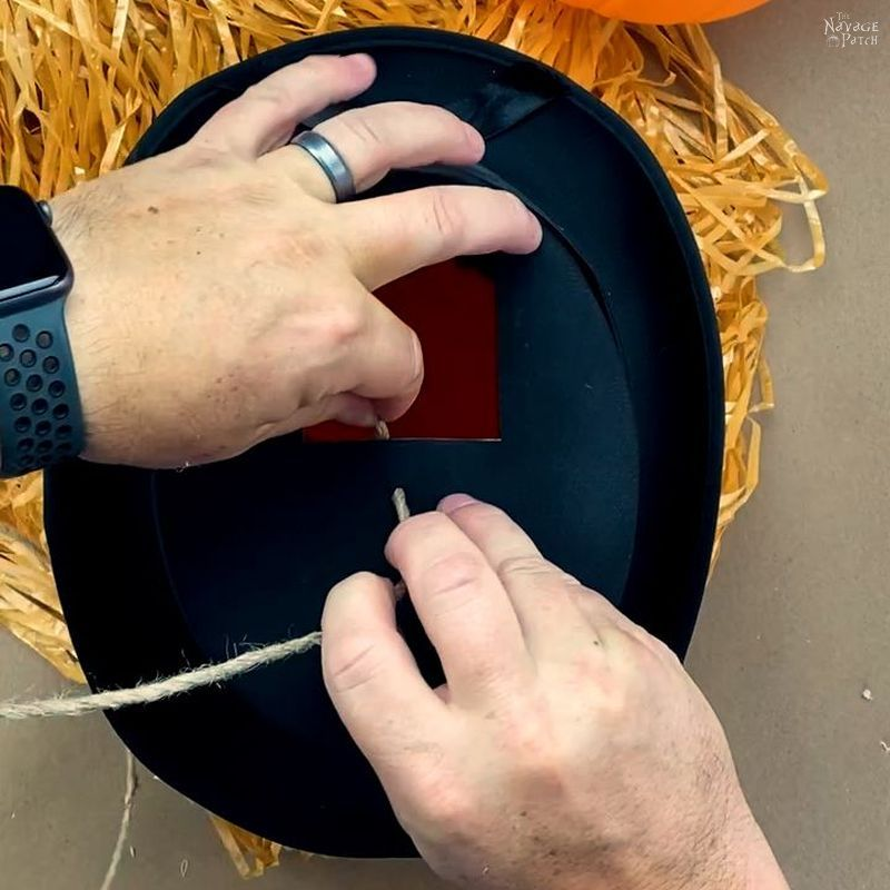 man sticking jute into a tope hat