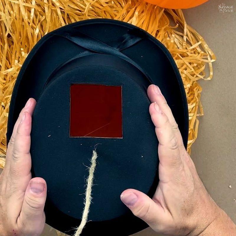 gluing a top hat on a raffia covered pumpkin