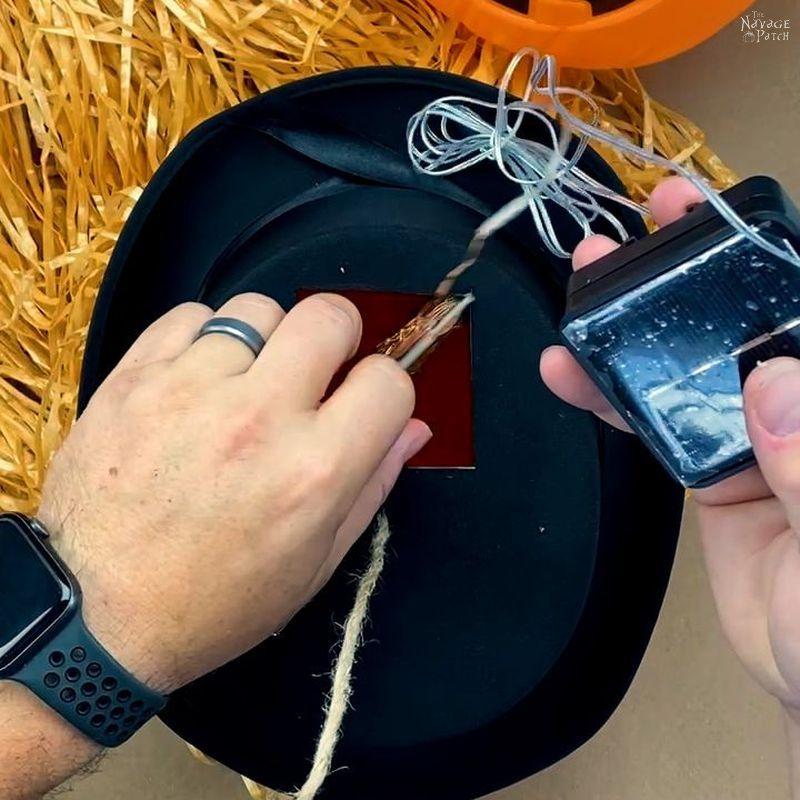 putting lights into a plastic pumpkin