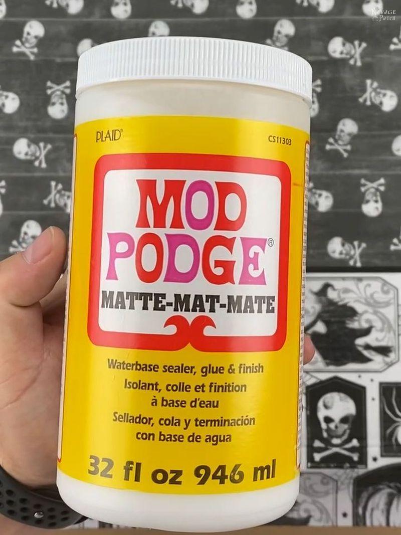 man holding a bottle of Mod Podge