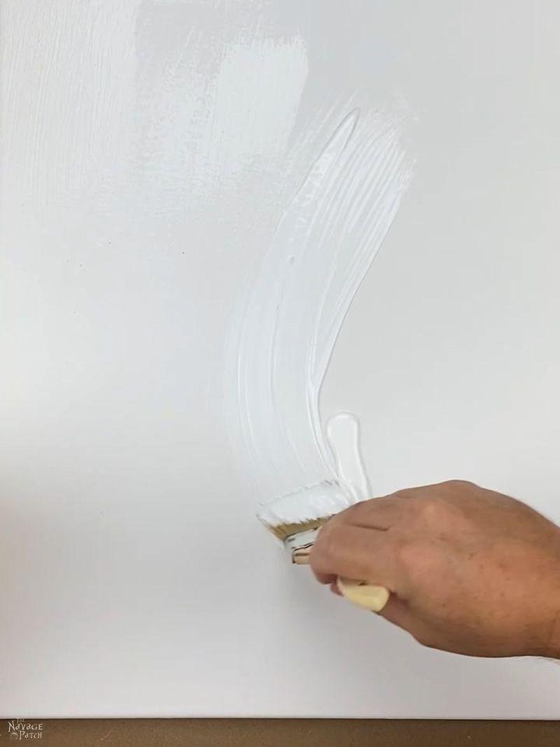 man brushing mod podge on a canvas