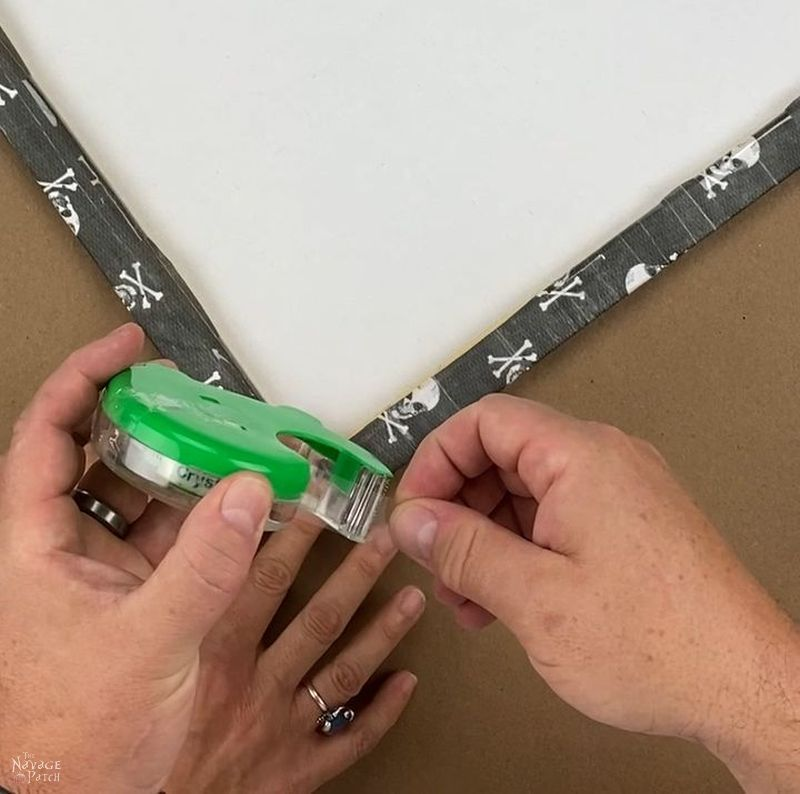 taping a table cover to the back of a frame