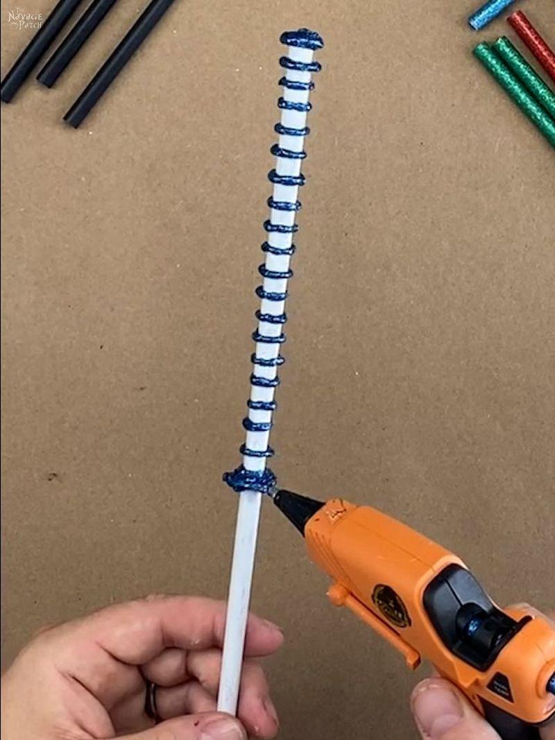 man putting blue glue rings around a white chopstick