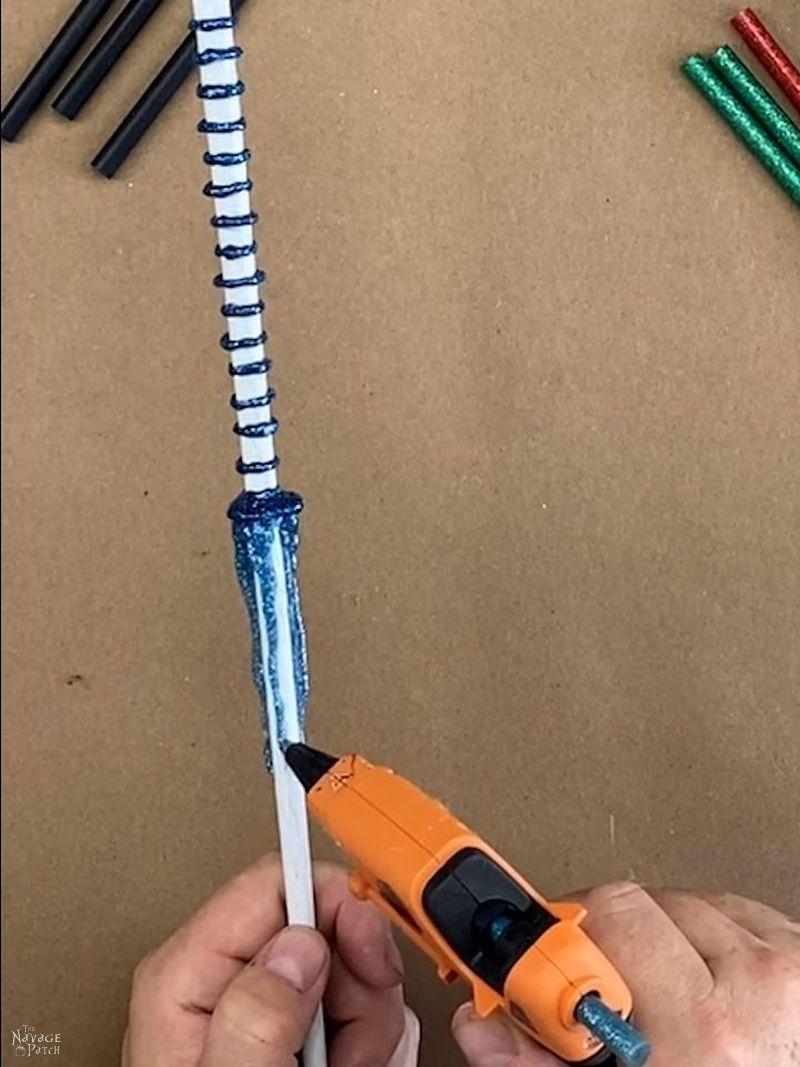 man putting blue glitter hot glue on a diy magic wand