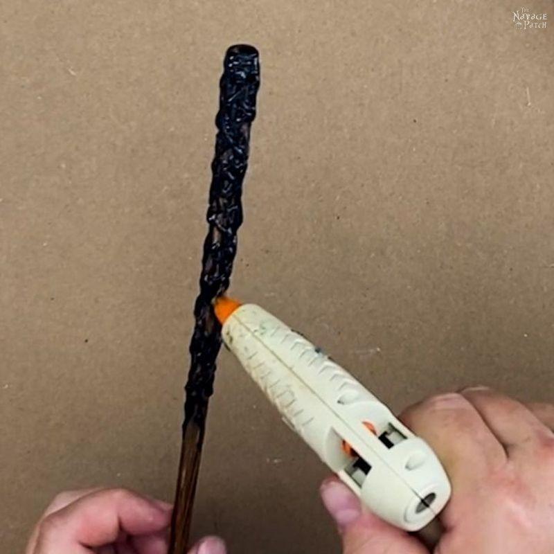 man putting black hot glue on a brown chopstick